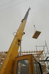 岐阜のFrameWork設計事務所の現場「大野町の家」の上棟の日、クレーンに吊られた合板