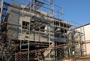 岐阜のFrameWork設計事務所の現場「各務原の家」コンクリート打ち放しの建物が足場に囲まれています。早く足場が外れて欲しい